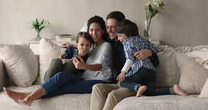Couple and children enjoy funny mobile application seated on sofa