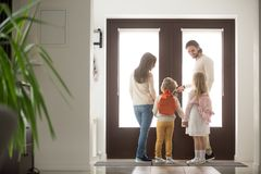 Couple with children in hallway gather for a walk. Married young couple with little preschool brother and sister standing in hallway near entrance door royalty free stock photos