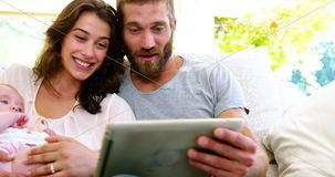 Couple with children looking at tablet computer. Outside stock footage