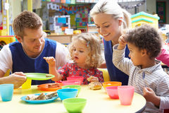 Couple and children playing. With food Royalty Free Stock Photos