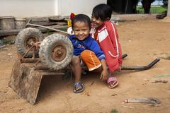 Two kids playing with a wheelbarrow royalty free stock photo