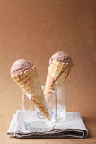 Couple of chocolate flavor ice cream cones in a glass on matte b Royalty Free Stock Photo