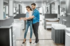 Couple chooosing new bathroom furniture in the shop. Young couple choosing new bathroom furniture at the plumbing shop with lots of sanitary goods royalty free stock photo
