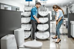 Couple chooosing new ceramic sink in the shop. Young couple choosing new bathroom sink at the plumbing shop with lots of sanitary goods stock photography