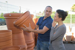 Couple choose pot for transplanting indoor plants. Couple choose a pot for transplanting indoor plants Stock Images