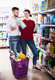 Couple choose some detergents. Young couple choose some detergents in the shop Stock Photography