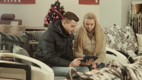 The couple chooses furniture using touchpad. In shop stock footage