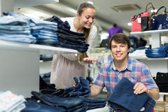 Couple chooses jeans at the shop Stock Photos