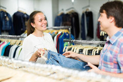 Couple chooses jeans at the shop Stock Photography