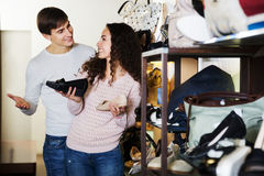Couple chooses summer women shoes. At fashionable shop royalty free stock photos