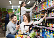 Couple choosing alcoholic beverages in shop Stock Images