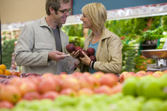 Couple choosing apples in grocery store Stock Images