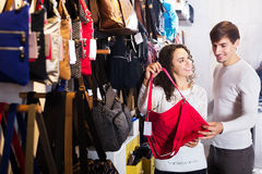 Couple choosing bags in shop royalty free stock photography