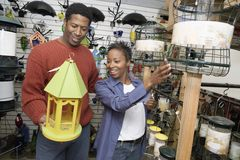 Couple Choosing Birdhouse In Store Stock Images