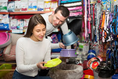 Couple choosing bowl in pet store. Happy young boyfriend helping smiling girl to choose bowl in pet store. Focus on girl Stock Photos