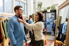 Couple choosing bowtie at vintage clothing store. Sale, shopping, fashion and people concept - couple choosing bowtie at vintage clothing store stock image