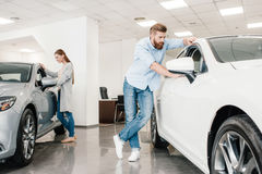 Couple choosing car, man and woman looking on various cars. Couple choosing car, men and women looking on various cars in dealership salon Royalty Free Stock Images