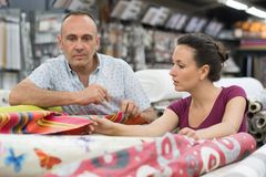 Couple choosing carpet holding up sample swatch Royalty Free Stock Photo