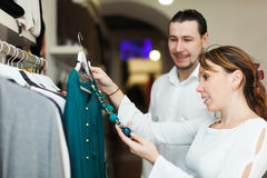 Couple choosing clothes at market Stock Image