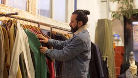 Couple choosing clothes at vintage clothing store stock video footage