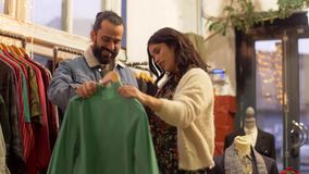 Couple choosing clothes at vintage clothing store stock video