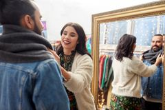 Couple choosing clothes at vintage clothing store. Sale, shopping, fashion and people concept - couple choosing clothes at vintage clothing store stock photo