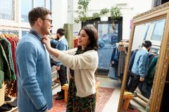 Couple choosing clothes at vintage clothing store royalty free stock photography