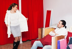 Couple choosing coat in fitting-room at market Stock Images