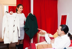Couple choosing coat in fitting-room at store. Couple choosing coat in fitting-room at clothing store Royalty Free Stock Photography