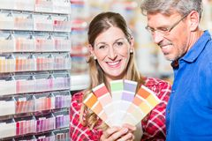 Couple choosing color of paint in hardware store. Couple, women and man, choosing color of wall paint in decoration department of hardware store Royalty Free Stock Photo