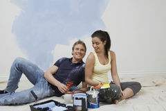 Couple Choosing Color From Swatches In Unrenovated House. Happy young couple choosing color from swatches on floor in unrenovated house Stock Image
