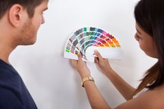 Couple choosing color for wall at new home Stock Photography