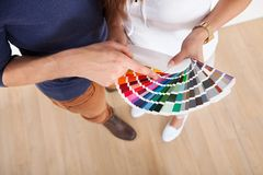 Couple choosing color for wall at new home royalty free stock images
