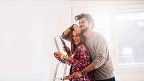 Couple choosing colors for painting home. Young couple choosing colors for painting home. Move in to new home. Happy young couple enjoying in their new empty royalty free stock photos