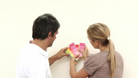 Couple choosing colours to paint new house stock video