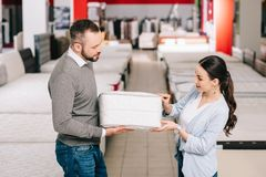 Couple choosing folding mattress together in furniture store. With arranged mattresses stock image