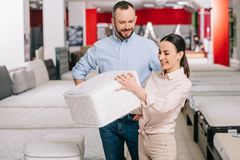 Couple choosing folding mattress together in furniture store. With arranged mattresses stock photo
