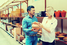 Couple choosing home dish-ware. Man and smilling women in atelier shop royalty free stock image