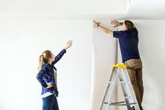 Couple choosing house wallpaper for wall stock photography