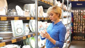 Couple choosing household goods in retailer. Consumerism, shopping, lifestyle. Handsome young Woman holding white plate, while standing in aisle with shelves of stock video footage