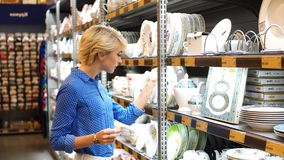 Couple choosing household goods in retailer. Consumerism, shopping, lifestyle. Handsome young Woman holding white plate, while standing in aisle with shelves of stock footage