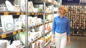 Handsome young Woman holding white plate, while standing in aisle with shelves of goods. Consumerism, shopping. Couple choosing household goods in retailer stock footage