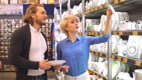 Couple choosing household goods in retailer. Consumerism, shopping, lifestyle. Young couple shopping. Handsome young couple choosing a gift for friends birthday stock video footage