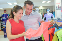 Couple choosing items in sport clothes shop Royalty Free Stock Image
