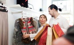 Couple choosing jacket at clothing shop Royalty Free Stock Photo