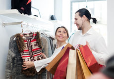 Couple choosing jacket at clothing shop Stock Images