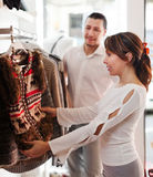 Couple choosing jacket at clothing shop Stock Image