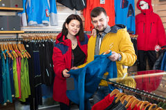 Couple choosing jacket in store Stock Photo