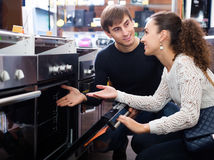 Couple choosing kitchen oven. Happy young couple choosing kitchen oven in store and smiling royalty free stock images