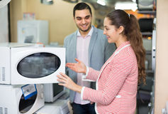 Couple choosing microwave oven Stock Photos